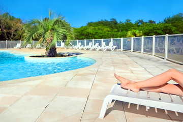 Female legs on a white sun lounger. Beautiful woman relaxing by the swimming pool with water against the background of tropical palm tree. Summer sunny day with clear blue sky