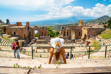 Jule 04, 2018. Taormina, Italy. Beautiful girl in a long white dress and white summer hat sitting at the caldron of the ancient Greek Theater of Taormina in Italy. Fototapete