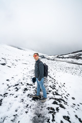 Young man hiking up the Etna volcano through the snow and fog.