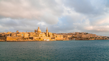 Panoramic view of Valletta Skyline at beautiful sunset from Sliema with churches of Our Lady of Mount Carmel and St. Paul's Anglican Pro-Cathedral, Valletta, Capital city of Malta