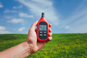 portable thermometer in hand measuring outdoor air temperature and humidity