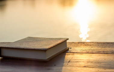 Notebook on the wooden Table with bokeh Sunset