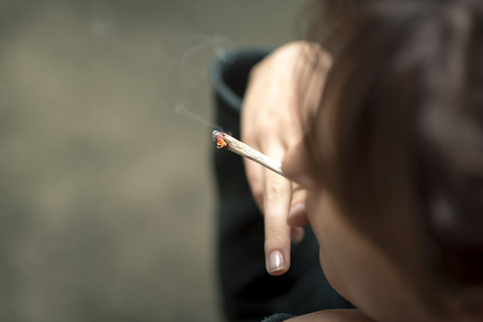 Young woman lighting a rolled joint of marihuana, closeup, smoking weed