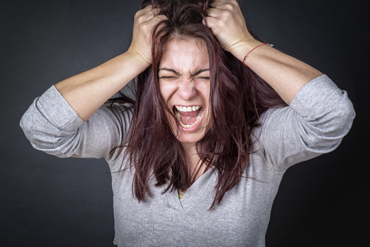Frustrated angry woman screaming and pulling her hair, young woman angry