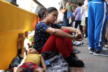 A 17-year-old Honduran mother seeking asylum and her 2-year-old son wait on the Mexican side of the Brownsville-Matamoros International Bridge after being denied entry by U.S. Customs and Border Protection officers near Brownsville