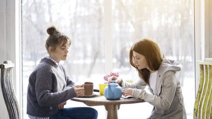 Two female friends adult girls sitting in front of each other drinking tea in a cafe holding closing a blue tea pot