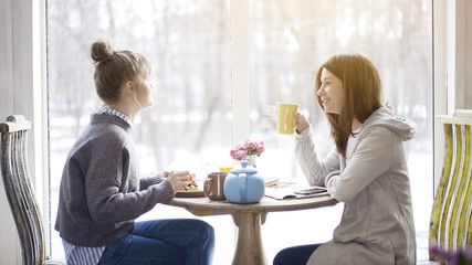 Two young adult female friends eating salad drinking tea sitting near a big window indoors in a cafe