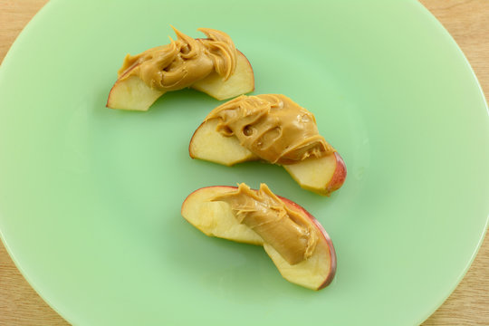 Close up of apple slices with peanut butter on green plate