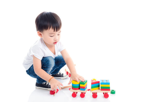 Little asian boy playing toy on the floor over white background