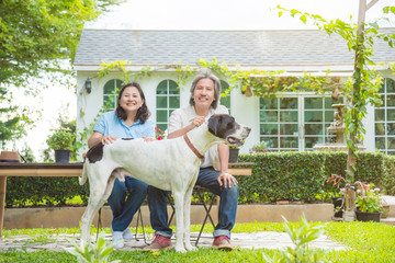 Retired couple sitting with dog in garden of their house and smile happily