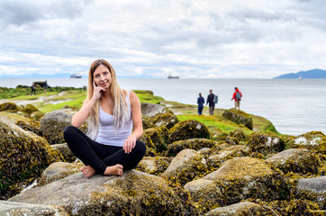 Young woman sitting on rock and smiling friendly into the camera in the intertidal zone of Vancouver, British Columbia