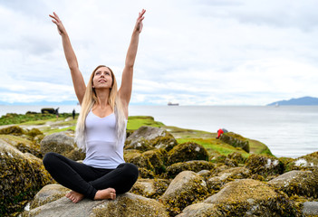 Young woman sitting on rock and her arms are raised into the air at the intertidal zone of Vancouver, British Columbia