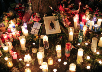 Candles and photographers of rapper Smoke Dawg surround a tree during a vigil in Toronto