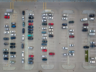 Aerial view of a large number of cars of different brands and colors standing in a parking lot near the shopping center in a chaotic manner. Parking divided by white dividing strips and sidewalks