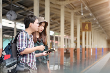 Backpacker woman and man stand at the train station with a traveler.Couple Travel concept.