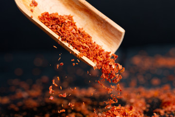 Spice red, ground, sharp bitter pepper is pouring out, a shovel is flying from a wooden scoop. Dark background