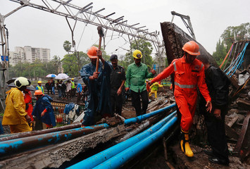 Rescue workers seen working at the site of an overbridge that collapsed over the railway tracks after heavy rains in Mumbai