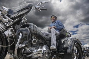 Elderly man sits on the back of a fancy three-wheeled motorcycle on a dark, stormy day