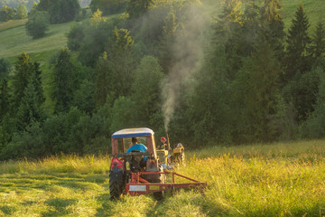 haymaking in the mountains, tractors with mowers cutting the meadows in the Polish mountains