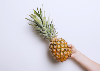 Woman's hand holding pineapple