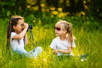 Two children girl hold a camera take a picture each other(together) with smile(happy)