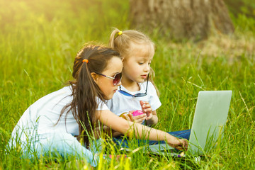 Two kids playing Laptop or Notebook in the garden for education. The concept is smart learning from internet and social media