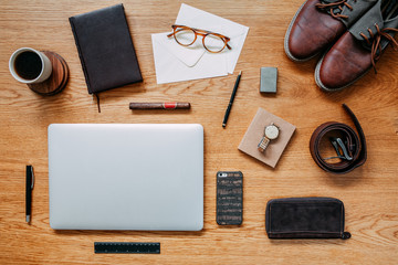 Modern and creative composition of flat lay on wooden desk with laptop, phone, shoes notebook, glasses and office accessories. Creative desk of traveler.