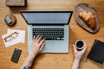 Modern and stylish composition of wooden desk with laptop, croissant, cup of coffee, phone, notebook, glasses and office accessories. Hands writing on laptop keyborad. Creative desk .Flat lay.