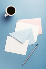 Group of colorful envelopes and a cup of coffee on blue table with empty card. Correspondence concept. Mockup.