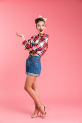 Full length portrait of an excited beautiful brunette pin-up woman