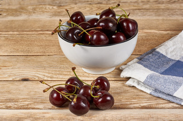 Cherries in a white bowl next to a doily and a few cherries in front, on a wooden background