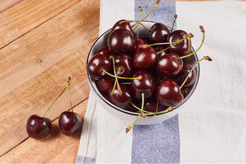 Cherries in a white bowl next to a doily and a two cherries in front, on a wooden background