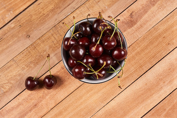 Cherries in a white bowl and a two cherries in front, on a wooden background