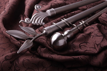 Metal ending for cornices and the folded fabric. Curtain rod and finials on the folded fabric