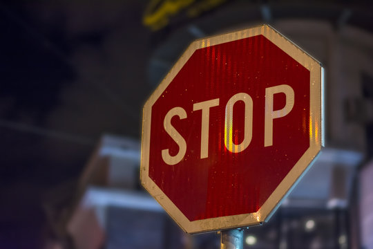Stop street night sign STOP on rod in the city