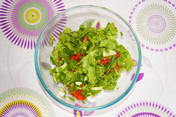 Salad with tomatoes, cucumbers, lettuce and green onions in bowl. Light coloured table on background. View from above.