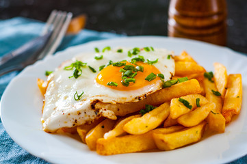 fried egg with potato in a white plate on table