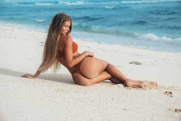View from the back of a young sexy girl in a bathing suit lies on the sand, looking at the seashore, enjoying her beautiful body.