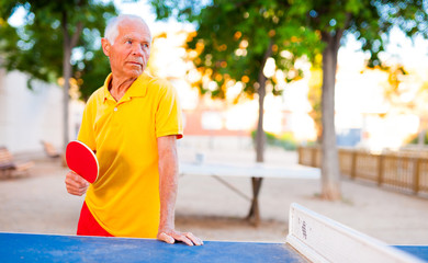 mature man posing with rackets at table tennis