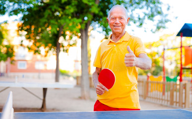 Happy mature man playing table tennis and showing thumb up