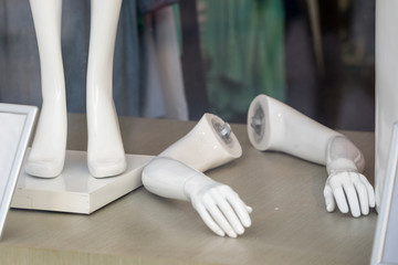 hand mannequin lying next to his feet in a clothing store