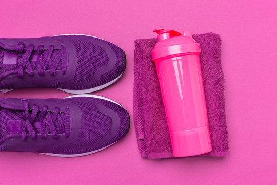 Pink plastic protein shaker cup on pink background
