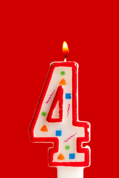 Colorful burning birthday candle  on red background