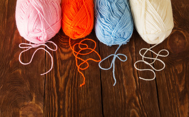 Skeins of yarn of different colors lie on wooden table