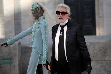 German designer Karl Lagerfeld appears with models at the end of his Haute Couture Fall/Winter 2018/2019 collection show for fashion house Chanel at the Grand Palais in Paris