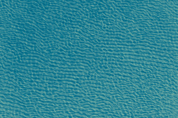 Beautiful sea background - sandy bottom with ripples in clear sea water, top view