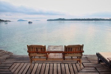 Two wooden chair on wooden floor with blue sea background