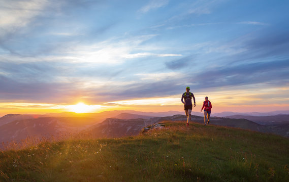 Two athletes trail running in Massif du Vercors during sunset. Shallow D.O.F.