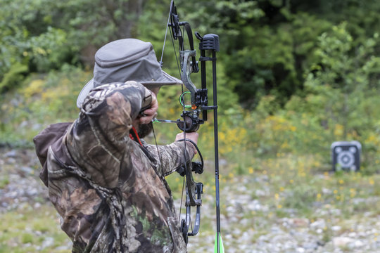 A Man Wearing Camouflage Shooting a Compound Bow