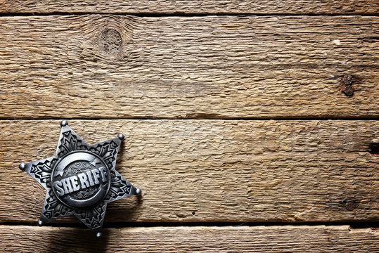 Sheriff star on wooden table closeup. Law concept background